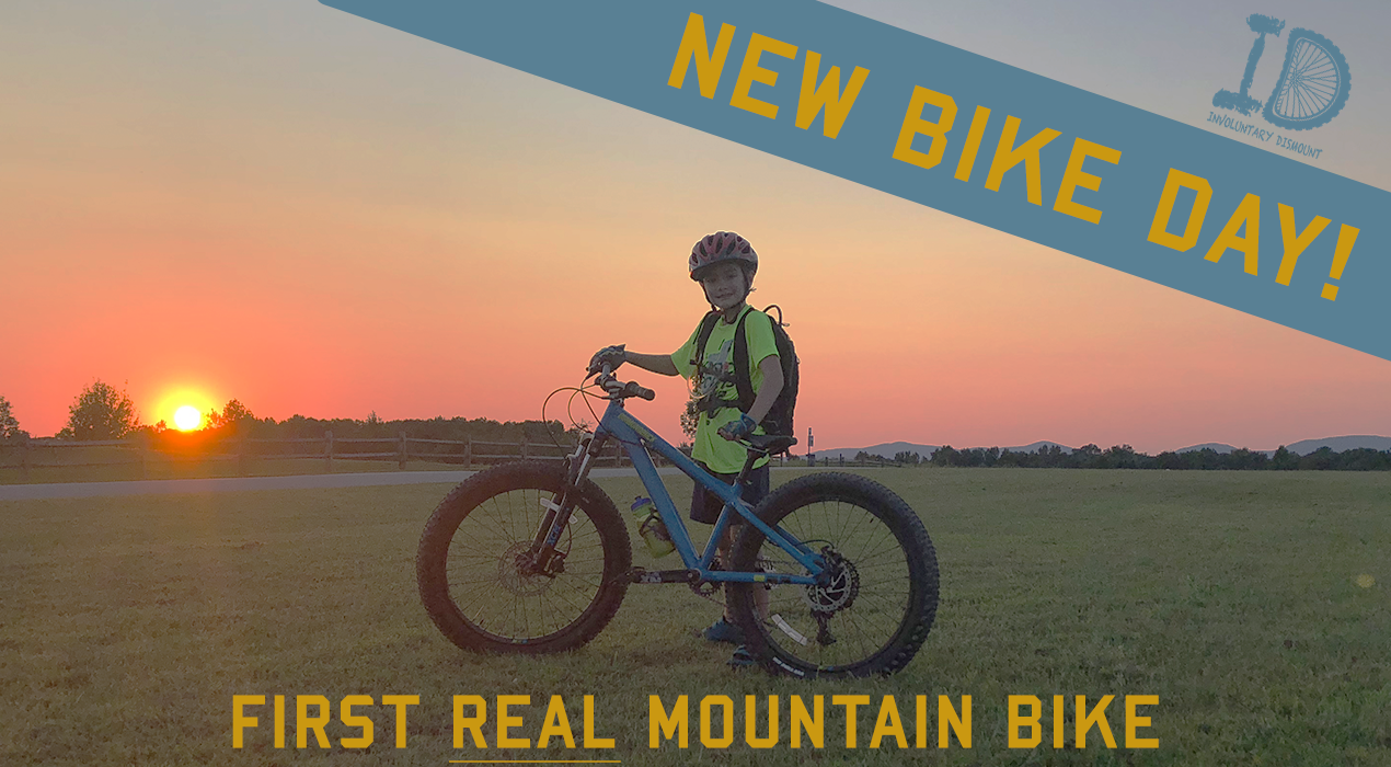 KID STANDING WITH BIKE AT SUNSET